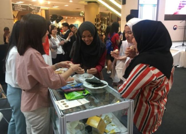 "Malaysian consumers enjoy a taste of South Korean ""gim,"" or dried laver, during the 2018 K-Food Fair in Kuala Lumpur in August. (Korea Agro-Fisheries & Food Trade Corp.)"