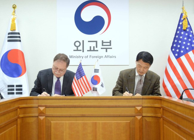 Chang Won-sam (right), South Korea's delegate to defense cost talks with the United States, exchanges a letter of accord with his counterpart Timothy Betts in a signing ceremony in Seoul on Sunday. (Yonhap)