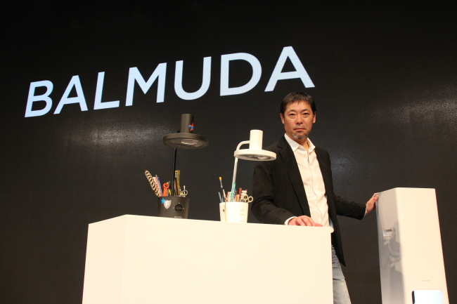 Balmuda CEO Gen Terao poses between The Light desk stands and The Pure, a new air purifier unveiled in Korea. (Lim Jeong-yeo/The Korea Herald)