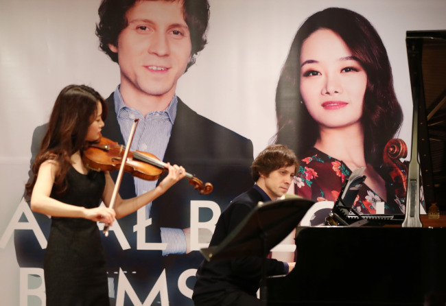 Violinist Kim Bomsori (left) and pianist Rafal Blechacz perform during a press event Tuesday at Munho Art Hall in Gwanghwamun, Seoul. (Yonhap)