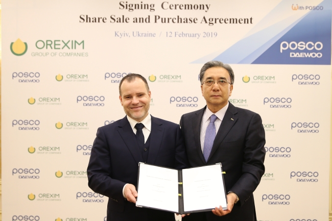 Posco Daewoo President Kim Young-sang (right) and Yuri Budnyk, chairman of Orexim Group, pose after signing a share sale and purchase agreement in Ukraine on Tuesday. (Posco Daewoo)