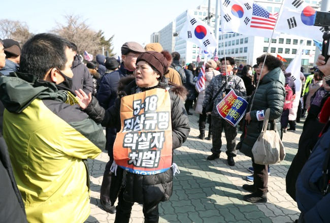 Family members of the deceased (left) on the verge of clashing with far-right Taegeukgi group over offensive May Gwangju uprising remarks made by lawmakers of the main opposition Liberty Korea Party at the National Assembly, Wednesday. (Yonhap)