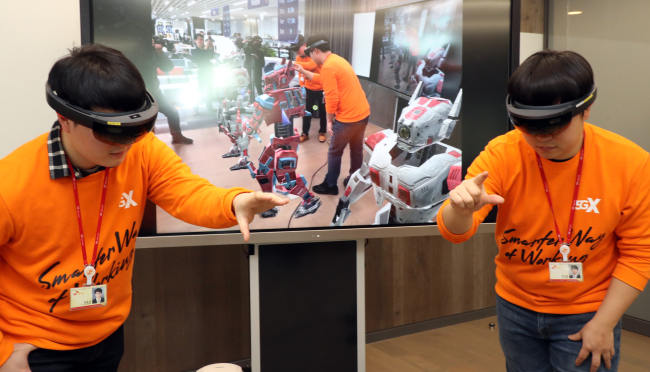 "SK Telecom workers demonstrate how to use the company's ""T-real telepresence,"