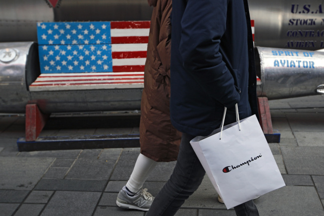 A couple carries a paper bag containing goods purchased from American brand Champion past a bench painted with the US flag at the capital city`s popular shopping mall in Beijing, Wednesday, Feb. 13, 2019. (AP-Yonhap)