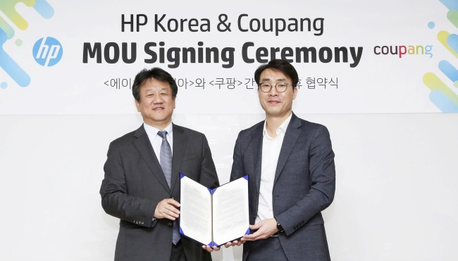 Coupang's Senior Director James BH Lee (right) and HP Korea Country Managing Director Kim Dae-hwan pose for a photo upon signing a strategic partnership agreement in Seoul on Thursday. (Coupang)