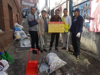 Yemeni asylum seekers and activist Kim Ki-hack pick up trash from the streets in Itaewon, central Seoul, near the Union of Yemen Community in Korea. (Union of Yemen Community in Korea)