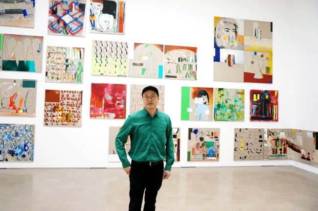 Artist Bek Hyun-jin poses for pictures in front of his paintings exhibited at PKM Gallery in Samcheong-dong, Seoul. (PKM Gallery)