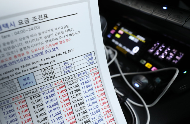 A table hung behind a taxi's front seat shows new cab fares. (Yonhap)