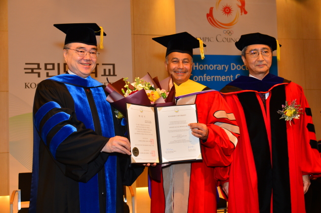 Husain Ali al-Musallam (center), director-general of the Olympic Council of Asia and first vice president of the International Swimming Federation, poses for photographs after receiving an honorary degree from Kookmin University on Monday. Kookmin University President Yu Ji-soo and Dean of Graduate School Park Chan-ryang are seen on the left and right, respectively. / Kookmin University