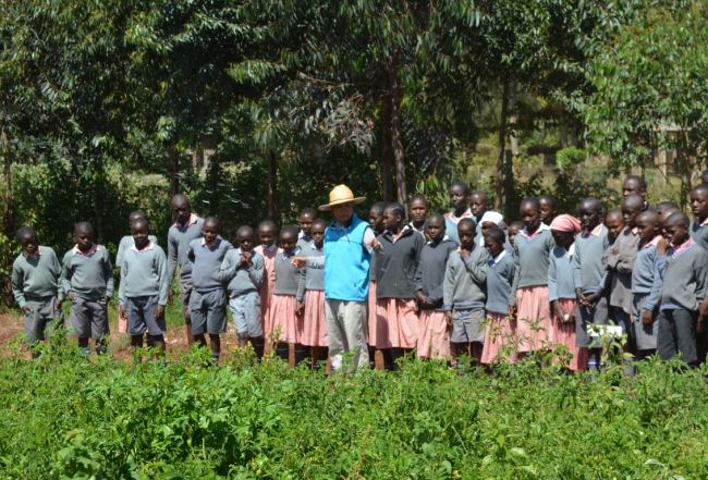 Former director of the Korea Program on International Agriculture, Kenya Center, Kim Choong-hoe, with students in a farm, fostered near Kandeng'wa Primary School in Kiambu county, Kenya. (KOPIA)