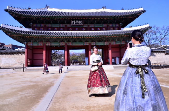 Visitors clad in traditional Korean hanbok take pictures in front of Donhwamun. (Park Hyun-koo/The Korea Herald)