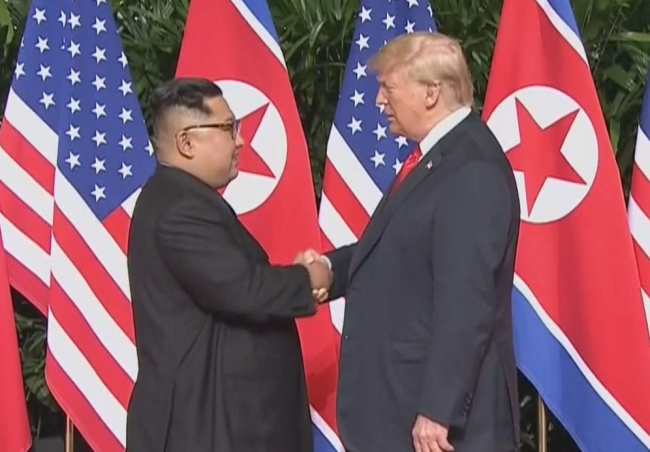 North Korean leader Kim Jong-un (left) shakes hands with US President Donald Trump (right) at the US-North Korea summit held in Singapore in June 2018. (Yonhap)