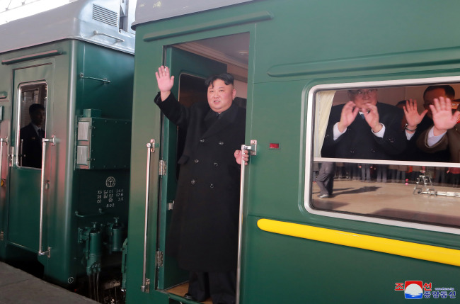 North Korean leader Kim Jong-un waves from the train bound for Hanoi at a train station in Pyongyang on Saturday. Yonhap