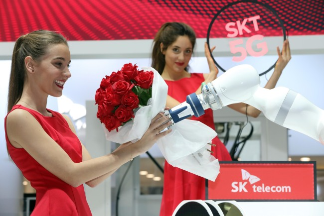 Models present various products featurng SK Telecom`s cutting-edge technologies at its booth set up at the MWC 2019 in Barcelona, Spain. (Yonhap)