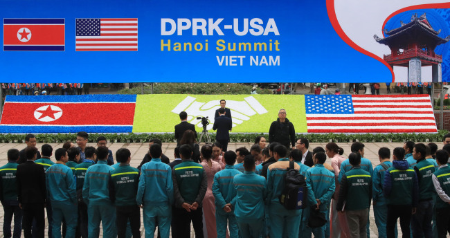 Vietnamese officials stand facing a sign installed for the US-North Korea summit in Hanoi on Sunday (Yonnhap)
