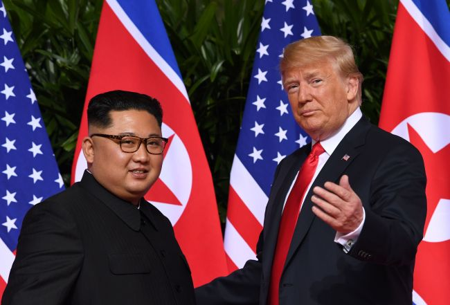 This file photo taken on June 12, 2018 shows US President Donald Trump (right) gesturing as he meets with North Korea's leader Kim Jong-un (left) at the start of their historic US-North Korea summit, at the Capella Hotel on Sentosa island in Singapore. (AFP-Yonhap)