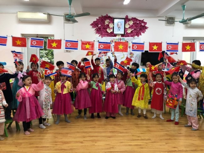 Children in traditional costumes sing and wave North Korean and Vietnamese flags at Vietnam-DPRK Friendship Kindergarten in Hanoi, Vietnam, Tuesday. (Jo He-rim/The Korea Herald)