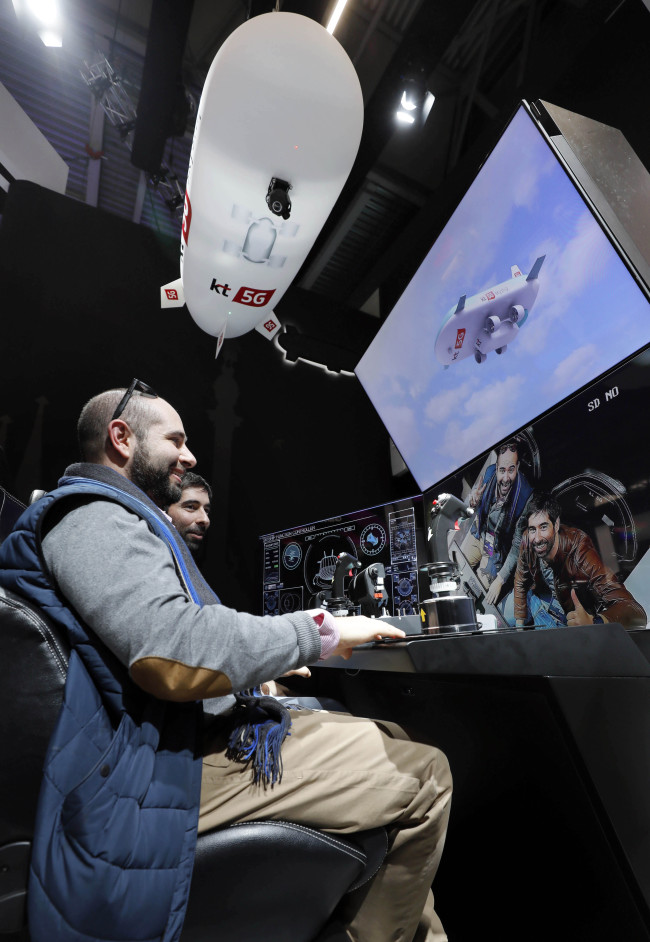Visitors take part in the 5G Skyship rescue platform utilizing drone technology and an airship at the KT booth set up at Fira Gran Via exhibition hall in Barcelona, Spain, Monday. (KT)