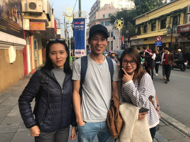 Vietnamese students Ngo Thao, Trinh Dang, Giang Yen (from left) wait in front of the Sofitel Legend Metropole Hanoi hotel to get a glimpse of the two leaders on Wednesday. (Jo He-rim/The Korea Herald)