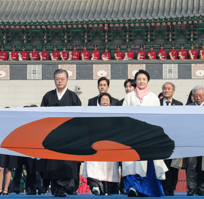 President Moon Jae-in and first lady Kim Jung-sook walk behind an older version of the national flag to enter a ceremony marking the centennial anniversary of the March 1 Independence Movement against Japanese colonial rule, at Gwanghwamun Square, Seoul, Friday. (Yonhap)