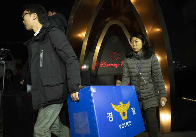 Officials of the Seoul Police leave after raiding famous nightclub Burning Sun located in Gangnam, southern Seoul, on Feb .14. (Yonhap)