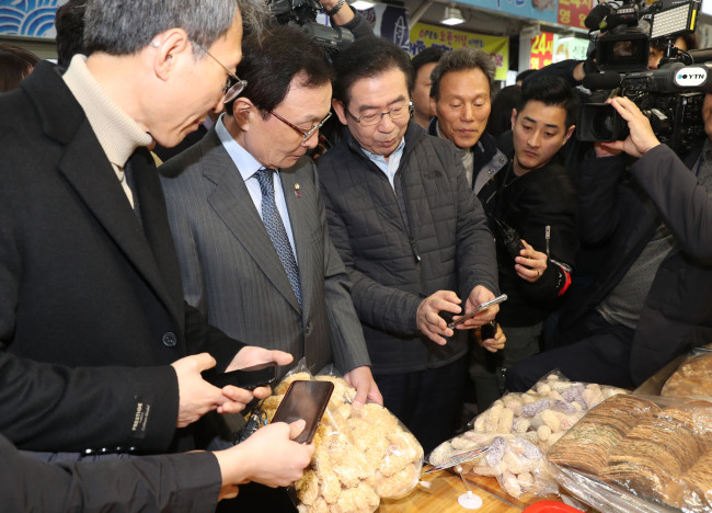 TESTING OUT ZERO PAY — Seoul Mayor Park Won-soon (third from left) and Rep. Lee Hae-chan (second from left), chairman of the ruling Democratic Party of Korea, purchase goods at the Sinwon Market in Gwanak-gu, Seoul, using Zero Pay, the city-led mobile payment system, Tuesday. Aimed at lowering card transaction fees for small merchants, Zero Pay lets users buy products by scanning a vendor's QR code. (Yonhap)