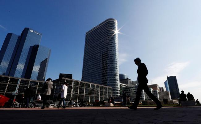 People walk on the esplanade of La Defense in the financial and business district of La Defense, west of Paris, France. (Reuters)