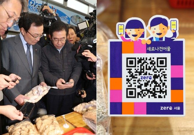 Seoul Mayor Park Won-soon (right) and Rep. Lee Hae-chan, chairman of the ruling Democratic Party of Korea, use Zero Pay to purchase goods at the Sinwon Market in Gwanak-gu, Seoul, Tuesday. (Yonhap)