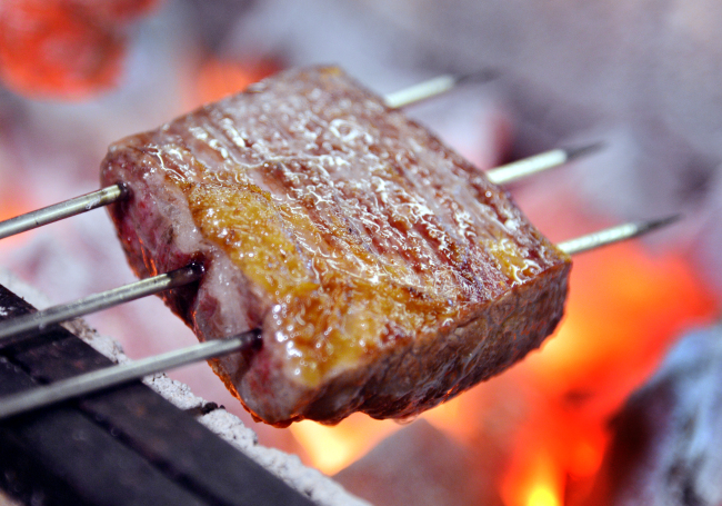 Patrons can watch the chefs in action, grilling meat like the flank steak pictured here as well as seafood and vegetables over hardwood charcoal. (Park Hyun-koo/The Korea Herald)