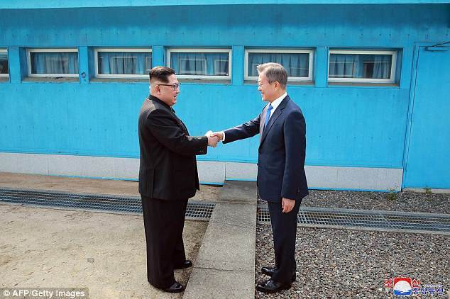 South Korean President Moon Jae-in (right) shakes hands with North Korean leader Kim Jong-un at the Military Demarcation Line that divides the two Koreas ahead of their summit at the truce village of Panmunjom, on April 27. (AFP-Yonhap)