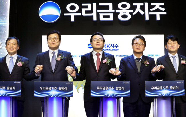 Woori Financial officials pose at a ceremony to mark the official transformation into a financial holding company at the headquarters in January. (Yonhap)