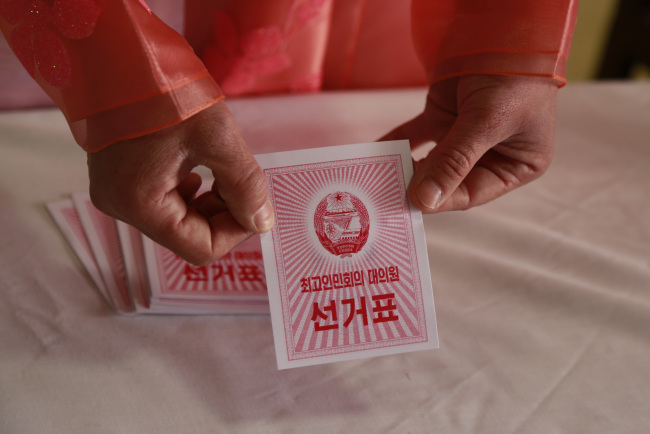 An electoral worker shows a ballot during the election at a polling station in Pyongyang, North Korea, Sunday. (AP-Yonhap)
