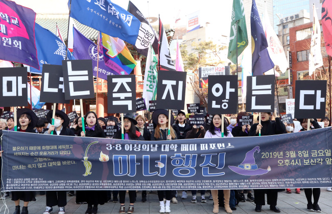 "Members of feminist clubs in colleges march to Gwanghwamun Square on March 8, holding signs saying ""Witches never die."" (Yonhap)"