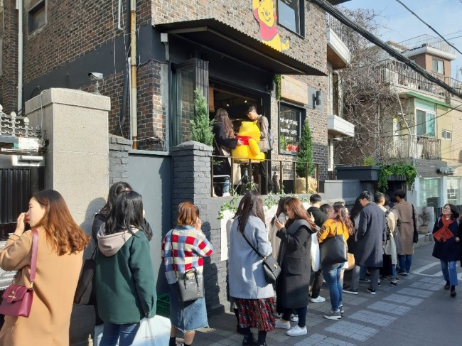 People wait in line outside a Winnie the Pooh pop-up store on Gyeongnidan-gil. (Shin Ji-hye / The Korea Herald)