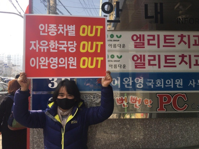 "An activist holds up a placard reading ""Racism OUT, Liberty Korea Party OUT, Rep. Yi Wan-young OUT"" in front of the lawmaker's office in Chilgok County, North Gyeongsang Province, on Feb. 22. (Gimhae Migrant Human Rights Center)"