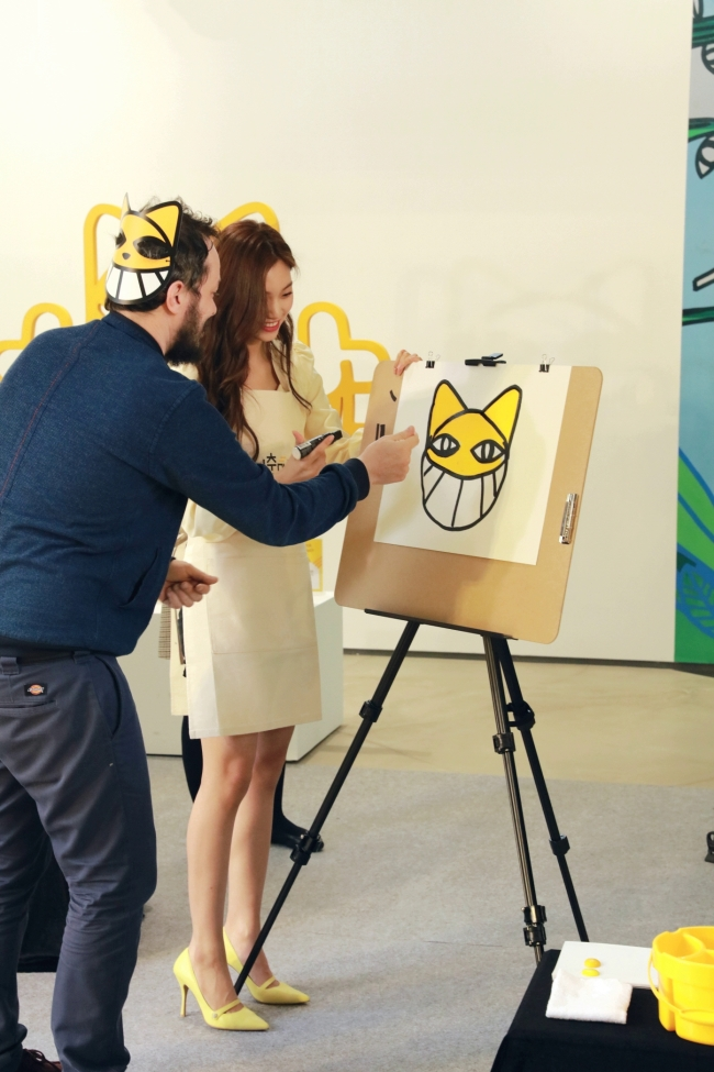 Thoma Vuille (left) and K-pop singer Doyeon work on a collaborative M. Chat painting at the KB Rockstar Youth Lounge in Hongdae, northwestern Seoul, Thursday. (KB Kookmin Bank)