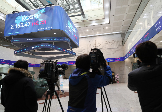 Reporters stand by at the Korea Exchange on Friday, as prosecutorial officials raid the bourse over its alleged involvement in Samsung BioLogics' accounting fraud case. (Yonhap)