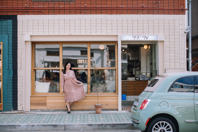 A woman poses outside a shop on Busan's trendy street Haeridan-gil. / Paradise Hotel Busan