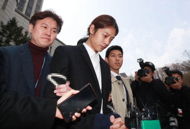 Police transfer singer Jung Joon-young (center) with his hands tied with a rope to Jongno Police Station after the warrant hearing at Seoul Central District Court on Thursday. (Yonhap)
