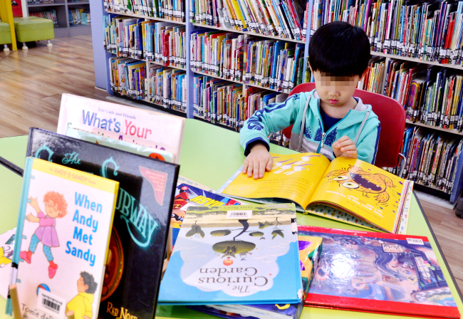 A child reads an English picture book inside Mapo English Literacy Center, a public library of English books for children in central Seoul. (Park Hyun-koo/The Korea Herald)
