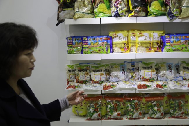 In this March 13, 2019, photo, a guide shows samples of food produced at Kumkhop Trading Co. displayed in its show room Pyongyang, North Korea. North Korean factories are filling city store shelves with ever better and fancier snack foods and sugary drinks, while government officials and international aid organizations warn the nation could be on the verge of a major food crisis. (AP Photo/Dita Alangkara)