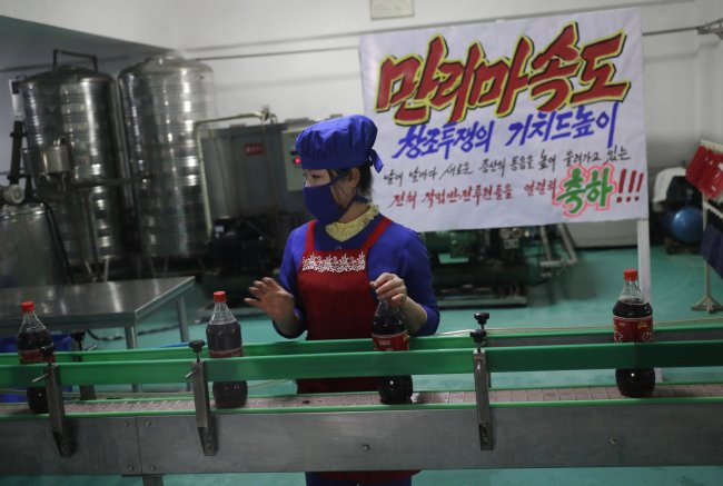 In this March 13, 2019, photo, a worker runs a conveyor belt moving bottles of soft drinks near a propaganda banner that reads