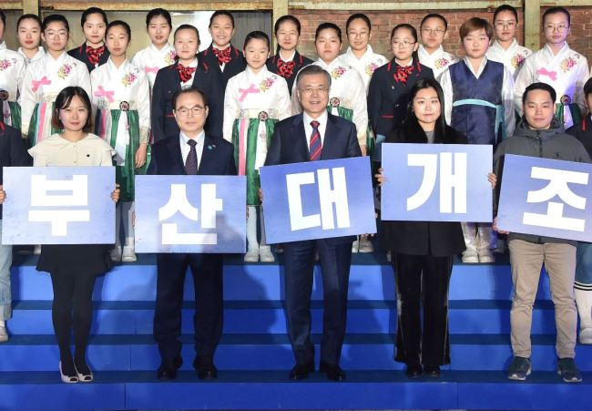 """President Moon Jae-in (center, front row) and Busan Mayor Oh Keo-don (second from left, front row) hold a card-section performance, which reads """"Full-Fledged Remodeling of Busan,"""" in Hakjang-dong of the port city on Feb. 13, 2019. (Busan City homepage)"""