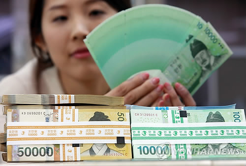 A commercial bank employee showcases a batch of fresh 10,000-won notes issued by the Bank of Korea. (Yonhap)