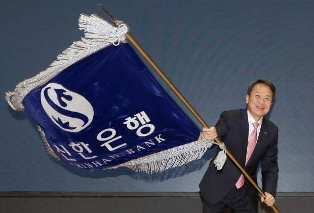 Shinhan Bank`s new CEO Jin Ok-dong waves the bank`s flag during his inauguration ceremony held at the bank`s headquarters in Seoul, Tuesday (Shinhan Bank)