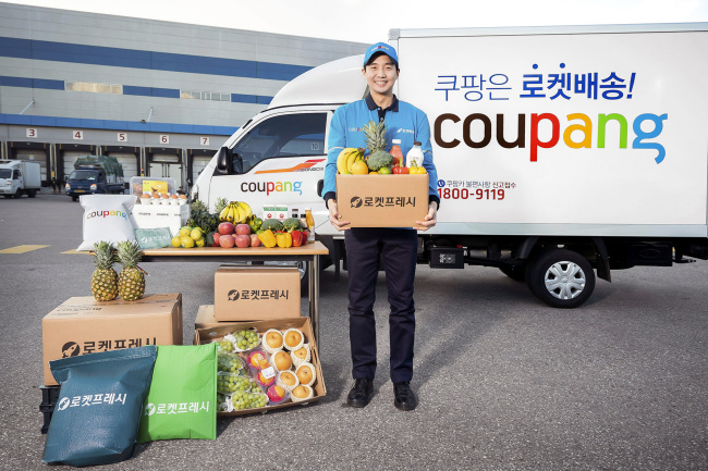 A Coupang worker poses for a photo with boxes for early-morning deliveries. Coupang
