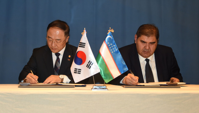 South Korean Deputy Prime Minister Hong Nam-ki (left) signs an agreement to start a joint study on a free trade pact with Uzbekistan on Thursday. (Yonhap)