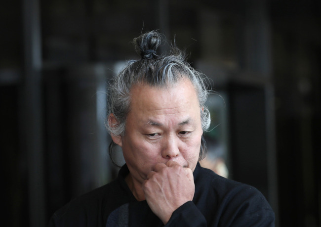 This file photo taken on June 12, 2018, shows South Korean filmmaker Kim Ki-duk listening to reporters` questions at the Seoul Central District Prosecutors` Office in Seoul. (Yonhap)