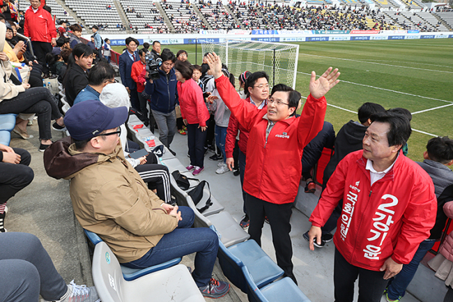 Main opposition Liberty Korea Party leader Hwang Kyo-ahn (center) and the party's Changwon district candidate Kang Ki-yoon greet spectators inside the Changwon Football Center, in violation of the K League's guidelines, on Saturday. (Yonhap)