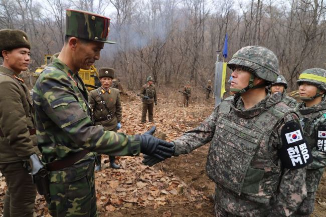 A South Korean (right) and a North Korean soldier shake hands as the two Koreas start building a road inside the Demilitarized Zone in Cheorwon, Gangwon Province, on Nov. 22. (Yonhap)